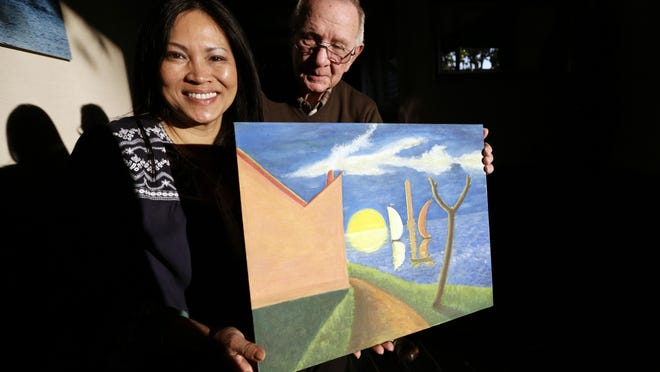 Erika Colligan holds a painting her father, Phan Khoi, painted during the Vietnam War for his Air Force flight instructor, Col. Billy Mobley, right.