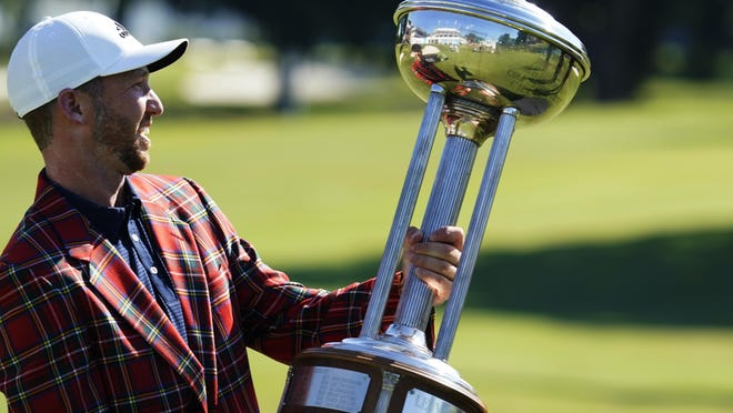 Daniel Berger poses with the championship trophy after winning the Charles Schwab Challenge golf tournament after a playoff round at the Colonial Country Club in Fort Worth, Texas, Sunday, June 14, 2020.