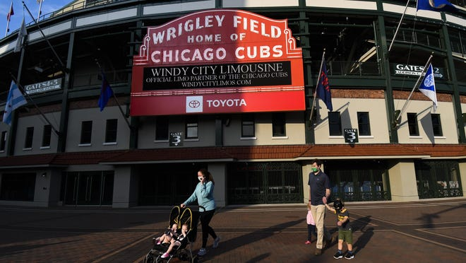 Individuals wear face masks and walk outside of Wrigley Field before a baseball game between the Chicago Cubs and the Minnesota Twins on Sunday, in Chicago.