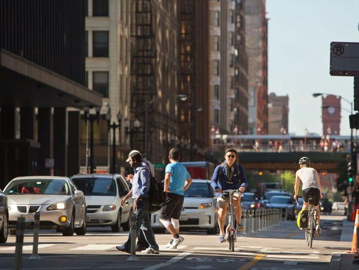 A cyclist travels north on Dearborn Street near Jackson Boulevard during the morning rush hour in Chicago. Cities for years have been touting bike lanes as a way to make cities more livable and help the environment, but car-dependent Americans increasingly are chafing over this trend as dedicated lanes become more common in big and small towns.
