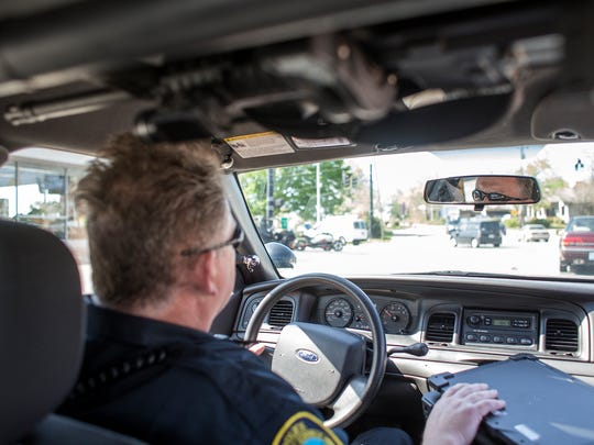Sgt. Charles Wells of the Asheville Police Department drives in his patrol car to Klondyke Homes for the first day of a new community policing effort in subsidized housing communities last week. Residents of the city's housing communities have struggled to get along with police in recent months, but are working together with police to improve relationships and make communities safer.