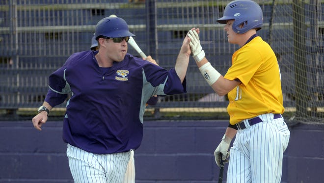 Benton head coach J.D. Stephens gives Josh Scherer a high five as he trots to third base
