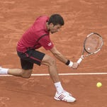 Novak Djokovic returns a shot during his 6-2, 6-1, 6-4 victory over Dominic Thiem on Friday.