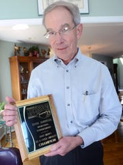 Art Smith holds a plaque from the Francis J. Robinson Memorial tennis tournament.