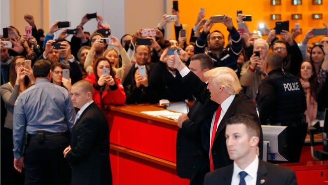 President-elect Donald Trump gives a thumbs-up to the crowd as he leaves the New York Times building following a meeting Nov. 22 in New York.