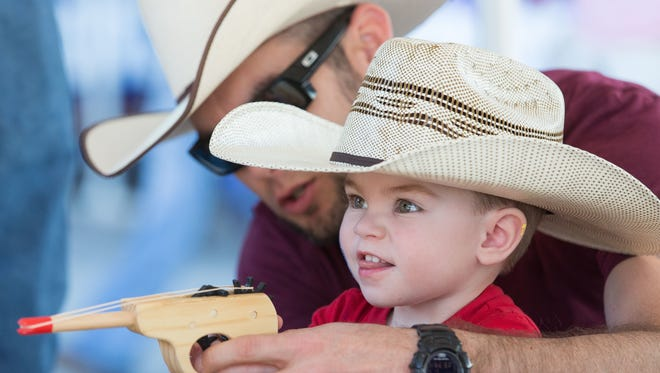 Brayden Jackson, 2, fires a rubber band gun at the Fort Selden Historic Site booth during the 18th annual Cowboy Days at the New Mexico Farm & Ranch Heritage Museum.