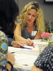 Stearns County public health coordinator Melissa Godwin works with her team during the United Way of Central Minnesota Access to Food event to figure out a budget for a low-income family on Wednesday at United Way of Central Minnesota.