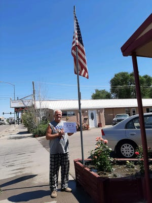 """Maurice Tuttle, Manager of Santa Fe Inn, receives his """"Fly Your Flag"""" award."""