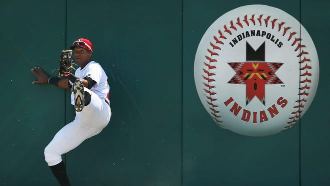 Indianapolis Indians outfielder Andy Vasquez checks the ball in the webbing of his glove after catching the ball at the outfield wall at Victory Field during the Indians' 6-5 victory over the Rochester Red Wings on Thursday, May 7, 2015. Down 4-0, Danny Ortiz' sacrifice fly scored the first run for the Red Wings in the top of the fourth inning.