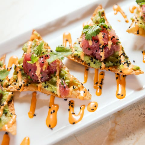 The tuna poke features wontons topped with ahi...