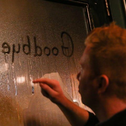 "Server Kyle Mock writes ""Goodbye!"" in the window..."