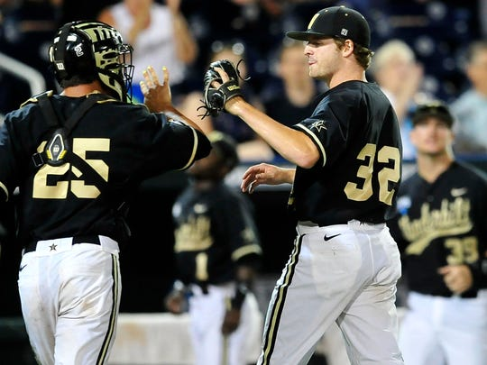 Vanderbilt pitcher Hayden Stone, right, gets a high-five from catcher Karl Ellison during the Commodores' 4-3 win over Texas at the College World Series.