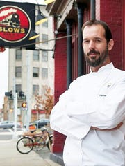 Slows Bar BQ chef and co-owner Brian Perrone poses in front of the restaurant's original Corktown home on Michigan Avenue.