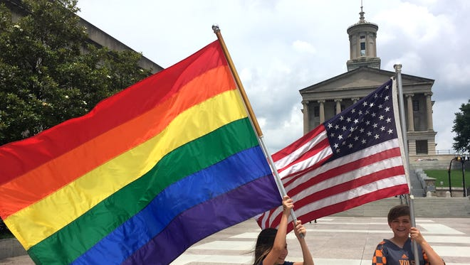Avery Roth, 10, and Sam Roth, 12, hold flag during a celebration at the state capital after U.S. Supreme Court officially recognized the legal authority for same-sex couples to be married on Friday June 26, 2015.