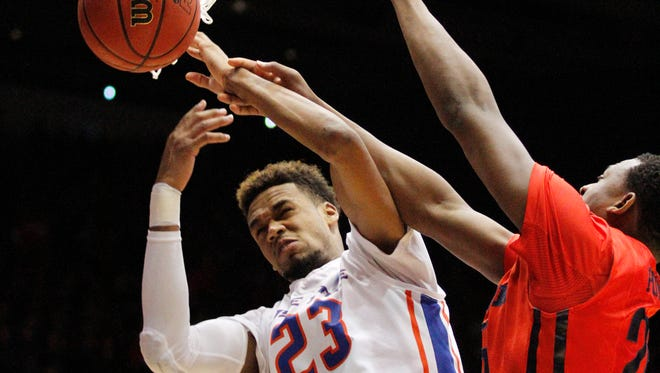 Boise State's James Webb III is hit by Dayton's Kendall Pollard in the First Four NCAA tournament basketball game Wednesday, March 18, 2015, in Dayton, Ohio.