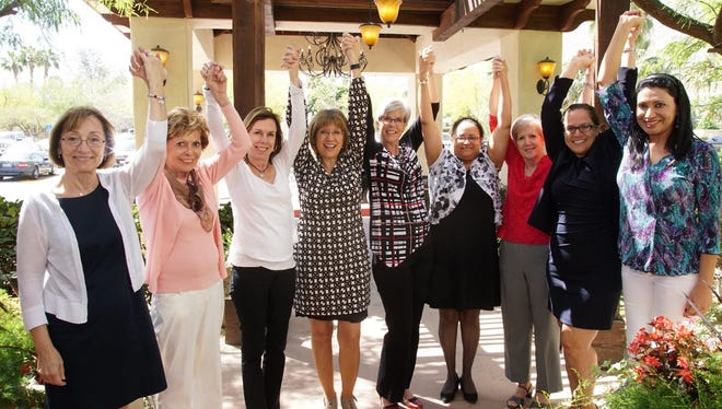 """(L to R) Phyllis Ruffalo, Karen Whitton, Paula Whitton, Teresa Whipple, Kim Gyngard, Julihana Madison, Susan Johnson, Claudia Fortiche, and Dr. Mona Khanna raise their hands at the inaugural luncheon of """"Nine girls ask? for a cure for Ovarian Cancer."""""""