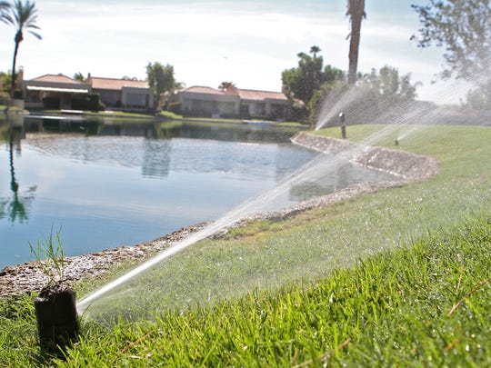 A sprinkler in the Lake Mirage Racquet Club waters the grass near one of the man-made ponds.