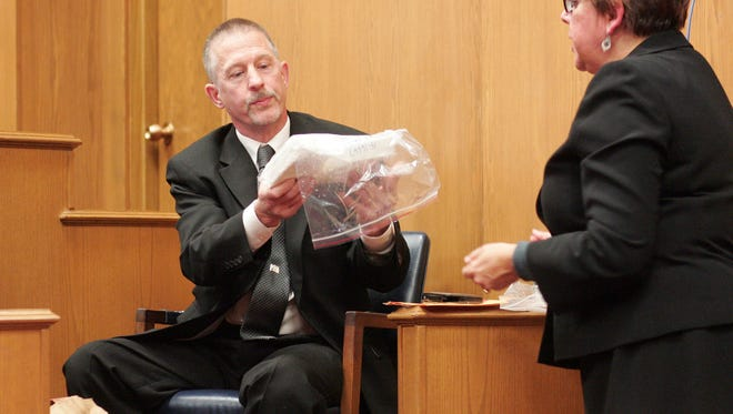 Paula Sawyers, right, assistant prosecutor, hands Lt. Paul Cortright, of CODE, a kilo of cocaine Ñ allegedly sent to Steven Smith Ñ Tuesday afternoon during Steven Smith's trial.