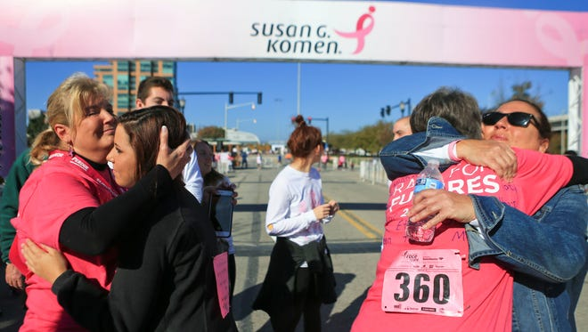 After crossing the finish line, Kim Lucas, left, gets a hug from daughter Kelsie Humphries during the 20th anniversary Susan G. Komen Race for the Cure event in Louisville Saturday morning. Lucas is a two-year survivor of breast cancer.