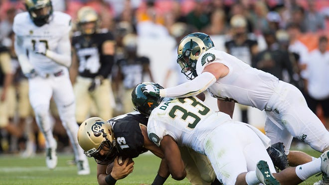 CSU defenders Kevin Davis and Jack Schlager take down CU quarterback Sefo Liufau during the Rocky Mountain Showdown at Sports Authority Field at Mile High Stadium in Denver Friday, September 2, 2016.