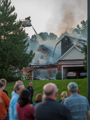 Neighbors watch as firefighters work to extinguish flames at a Perinton townhouse on Onyx Drive.