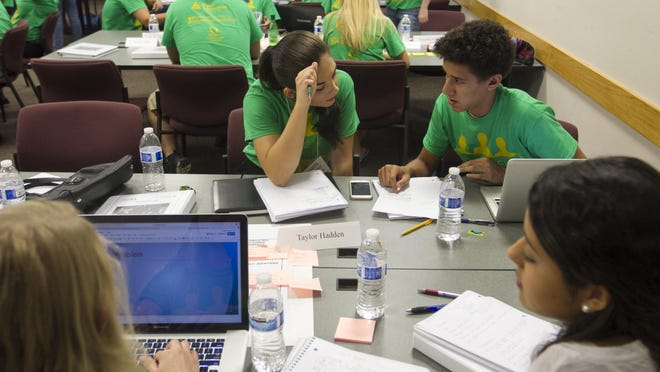 Taylor Hadden, center, and Gunnar Scott and their teammates work on the plan for their app designed to protect consumers from credit card fraud and theft on Wednesday during CEO Academy at FGCU.