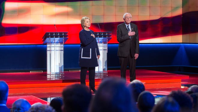 Hillary Clinton and Bernie Sanders stand during the national anthem before the Democratic debate in Flint, Mich., on March 6, 2016.