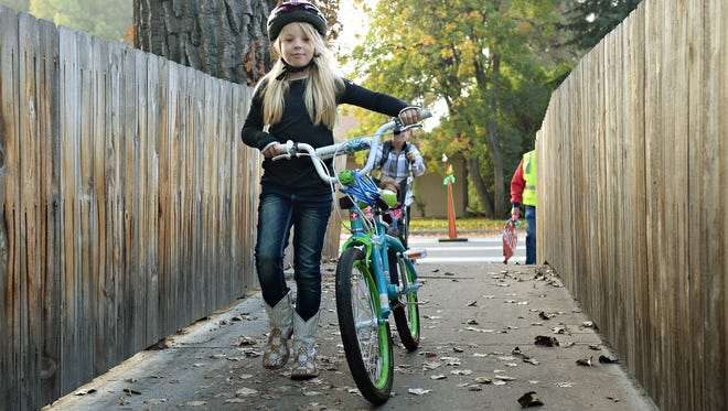 Lily Ellis, 6, walks her bike through an alley to Laurel Elementary on National Walk/Bike to School Day, Wednesday, October 7, 2015.