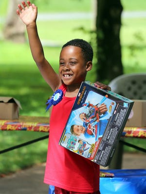 Tre'Mars Dillard waves as a parade of local fire departments, EMS and law enforcement drive by his home for his Make-A-Wish Day on Thursday.