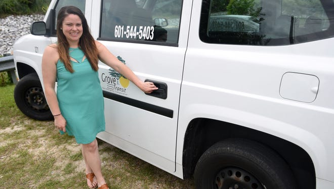 """Callan Reid, vice president for Grove Transit, stands by one of the company's vehicles. Grove Transit has launched groveRideNow, an """"Uber-like"""" app-based pickup service."""
