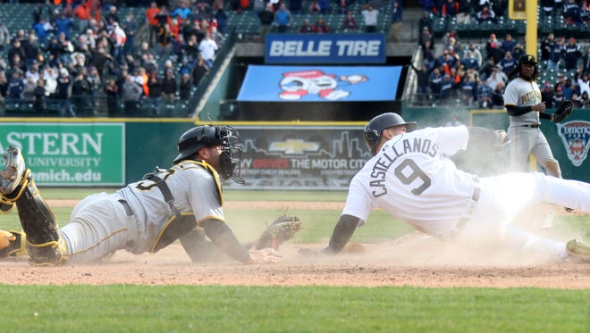 Detroit Tigers right fielder Nicholas Castellanos slides past Pittsburgh Pirates catcher Francisco Cervelli in a contested play in the tenth inning as the Detroit Tigers take on the Pittsburgh Pirates at Comerica Park for Opening Day in Detroit Friday March 30, 2018.