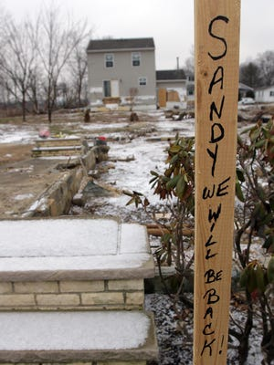 In this February 2013 photo, a sign is planted near the foundation of a Union Beach home washed away by superstorm Sandy.
