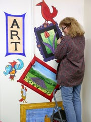 Debby Denno works on a mural outside the Red Raven Gallery in downtown Salem on Thursday, Feb. 25, 2016. The finished mural, with paintings by four different artists, will be unveiled during a reception at the gallery on Wednesday, March 2 from 5 p.m.-8 p.m.