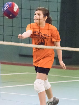 Mallory Beckwith, 8, serves during a Wattles Park Men's Club youth volleyball game at the Battle Creek YMCA.