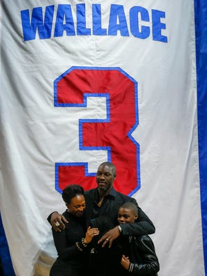 Former Detroit Piston Ben Wallace, wife Chanda and children, Bryce, and Bailey, stand in front of his jersey that was retired to the rafters during halftime at the Palace of Auburn Hills on Jan. 16, 2016.