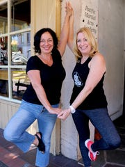 From left, Zohra Campbell and Meg Britton of Indigo Wellness Center strike a yoga pose.