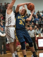 Greencastle's Bryan Gembe (32) takes a shot while Shippensburg's basketball player tries to block the shot during a boys basketball game on Friday, Jan. 6, 2016, at Shippensburg. Greencastle defeated Shippensburg 72-51.