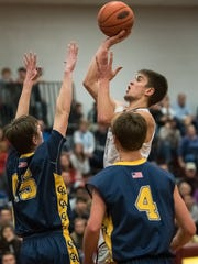 Shippensburg's Cody Gustafson (10) takes a shot while being guarded by Grencastle's Ian Gelsinger (15) and Brandon Stuhler (4) during a boys basketball game on Friday, Jan. 6, 2016, at Shippensburg. Greencastle defeated Shippensburg 72-51.