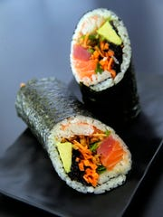 The Titan sushi burrito is made with tuna, salmon, kani, avocado, jalapeno, onion crisps, cilantro, mayo and poké sauce.