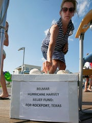 Pam Martin, Wall Township, makes a donation into the 5th Avenue beach access box Monday, September 4, 2017, that will previde Hurricane Harvey relief to Rockport, Texas.  Access to the beach was free on Monday, instead hurican relief donations were accepted.