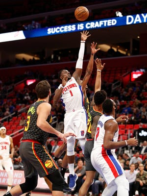 Pistons guard Reggie Jackson shoots over Hawks forward John Collins (20) and guard Kent Bazemore (behind) during the first quarter of the Pistons' 111-104 win Friday at Little Caesars Arena.