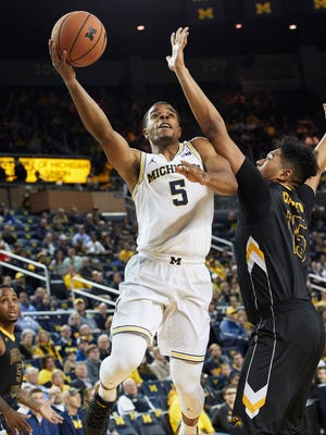 Michigan guard Jaaron Simmons shoots over Southern Miss forward Eddie Davis III in the first half at Crisler Center on Thursday night.