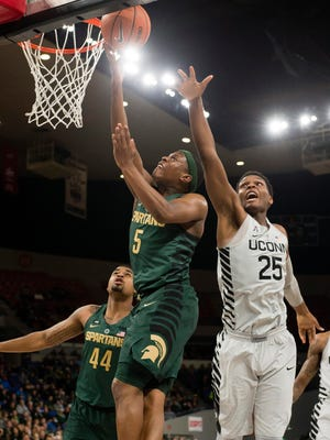 Michigan State guard Cassius Winston (5) scores a basket as he is defended by Connecticut forward Josh Carlton (25) during the first half during the Phil Knight Invitational tournament on Friday, Nov. 24, 2017, in Portland, Ore.