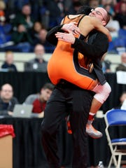 Sprague's Bollong Joklur jumps into the arms of coach Nolan Harris after winning the OSAA Wrestling Class 6A state championship final for weight 106 at Veterans Memorial Coliseum in Portland on Saturday, Feb. 17, 2018.
