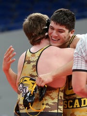 Cascade's Louis Sanchez, right, hugs teammate Macoy Christman after they competed in the OSAA Wrestling State Championships Class 4A final for weight 220 at Veterans Memorial Coliseum in Portland on Saturday, Feb. 17, 2018. Sanchez was the champion.