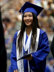 A graduate receives her diploma during the McNary High School commencement at the Oregon State Fairgrounds in Salem on Friday, June 8, 2018.