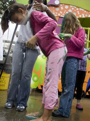 2007: Nickelodeon's Slime Across America Cross-Country tour comes to Six Flags Great Adventure. A Nickelodeon employee Thalia Sirjue 23 of Somerset (left) cleans Lily Stadler 9 of South Brunswick off after being repeatedly slimed. Anna Lombardo 9 of Florence NJ waits her turn to the right.