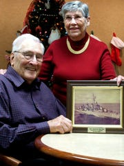 Al Sackett is shown here in 2014 with his wife Patt, displaying a treasured photo of his first destroyer command, the USS Preston.