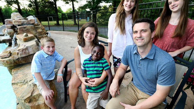 The Rosser family together on their back patio, on Thursday, June 16, 2016. Front row (L to R) Knox Rosser, 11, Abby Rosser, Ezra Rosser, 5, and Brent Rosser. Back row Ella Rosser, 14, and Lucy Rosser. The family has waited a long time to get their adopted son/brother Ezra Rosser, out of the Congo so they can all be together.