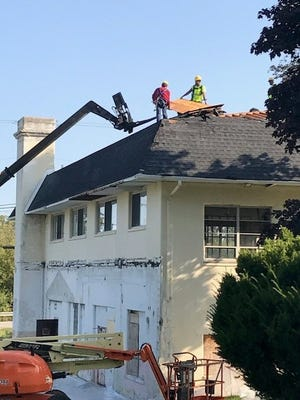 Crews work on the roof of the arts factory on the old Ford property in Cherry Hill Village.